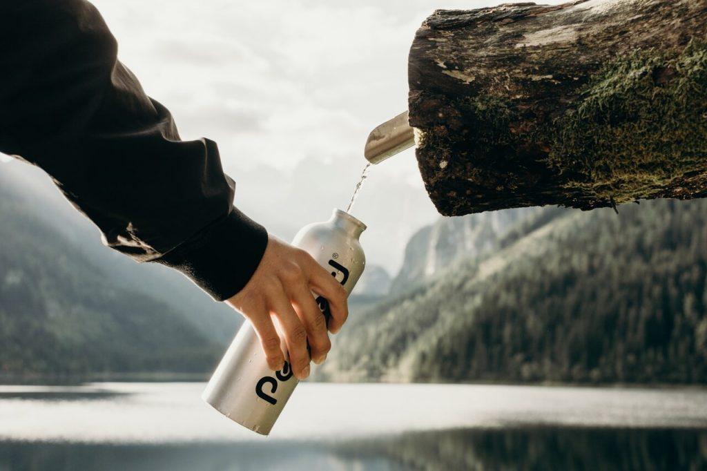 Auffüllen einer Wasserflasche am Brunnen